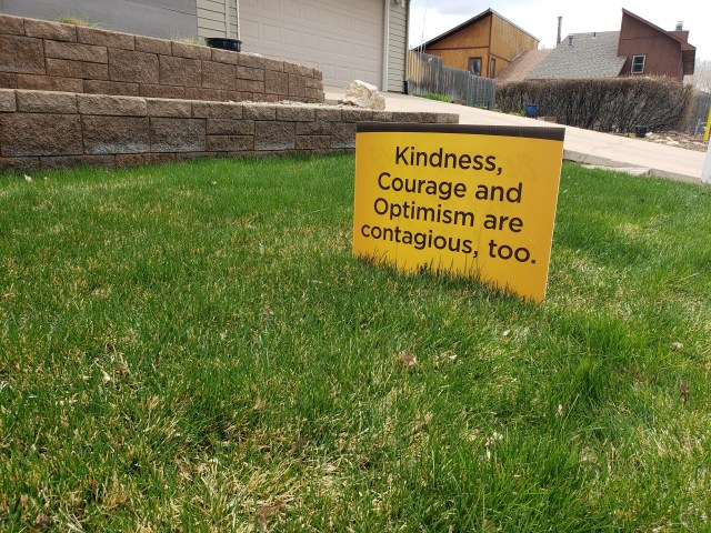"UW yard sign found on lawn in Laramie, Wyoming, during the coronavirus pandemic encourages a sense of community. It reads, ""Kindness, Courage, and Optimism Are Contagious, Too."" Photo taken by AHC Archivist Sara Davis."