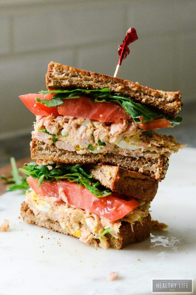 This Yellowfin Tuna Salad Sandwich made with high quality tuna, egg, dijon, a bit of spice all a top the perfectly toasted piece of bread and then topped with greens and a slice of heirloom tomato may be the best tuna salad sandwich ever | ahealthylifeforme.com