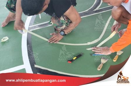 menempelkan selotip isolasi pada tanda pensil yang sudah digambarkan di lantai olahraga