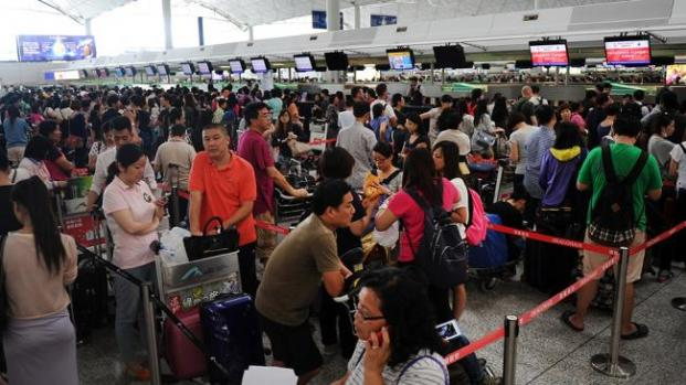 Passengers queue to register at an airline counter as Typhoon Usagi approaches at Hong Kong airport on Sept. 22, 2013. (AFP/Getty Images)