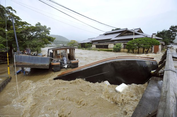 An overturned sightseeing boat is stuck by a bridge after the Katsura River was overflooded by torrential rains caused by a powerful typhoon in Kyoto, western Japan, Monday, Sept. 16, 2013. Typhoon Man-yi, one of the most powerful storms to lash Japan this season, was bearing down on Japan and went past Tokyo on Monday, leaving one dead and dumping torrential rains, damaging homes and flooding parts of the country's popular tourist destination of Kyoto, where hundreds of thousands of people were ordered to evacuate to shelters. (AP Photo/Kyodo News)