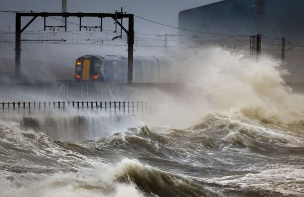 Waves crash against the railway embankment as a train edges along the coast at Saltcoats in Scotland. (PA)
