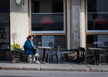 A woman sits with a glass of wine at a table outside a restaurant, as the spread of the novel coronavirus continues, in Stockholm, Sweden April 17, 2020. Stina Stjernkvist / TT News Agency/via REUTERS      ATTENTION EDITORS - THIS IMAGE WAS PROVIDED BY A THIRD PARTY. SWEDEN OUT. NO COMMERCIAL OR EDITORIAL SALES IN SWEDEN.