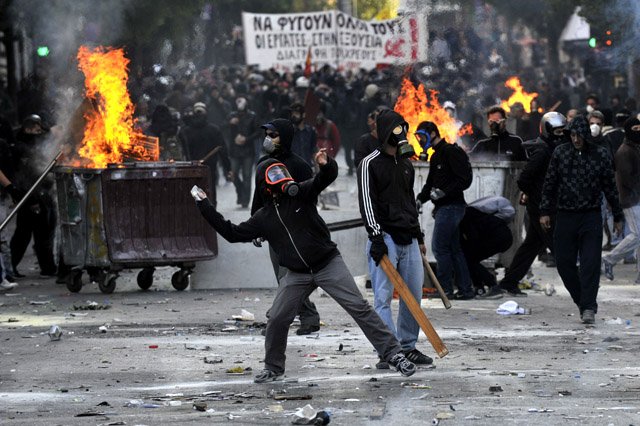 Police clash with masked demonstrators  in Athens on October 20, 2011. Clashes have broken out in central Athens between rival groups of demonstrators, amid a second day of mass demonstrations against a new round of austerity measures being debated in parliament. Police fired tear gas and stun grenades outside parliament as several hundred masked youths attacked peaceful demonstrators from a Communist-backed trade union who had tried to isolate them from the rally. AFP PHOTO / LOUISA GOULIAMAKI