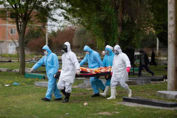 QAEM SHAHR, IRAN - APRIL 10: Volunteers in protective suits bury the body of a COVID-19 victim on April 10, 2020 in Qaem Shahr, Iran. The Coronavirus (COVID-19) pandemic has spread to many countries across the world, claiming over 100,000 lives and infecting over 1.8 million people. There have been over 4,000 deaths and over 70,000 people infected with the coronavirus (COVID-19) in Iran so far. (Photo by Majid Saeedi/Getty Images)