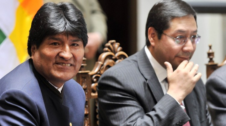 Bolivian president Evo Morales (L) and Economy Minister Luis Arce Catacora  during a ceremony to launch USD 500 million in bonds on October 23, 2012 at the Palacio Quemado presidential palace in La Paz.     AFP/PHOTO/Aizar Raldes (Photo by AIZAR RALDES / AFP)