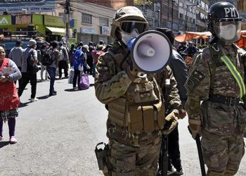 A military policeman uses a loudspeaker to tell people to go home during a total lockdown ordered by the government until April 15 in El Alto, Bolivia, on April 3, 2020. (Photo by AIZAR RALDES / AFP)