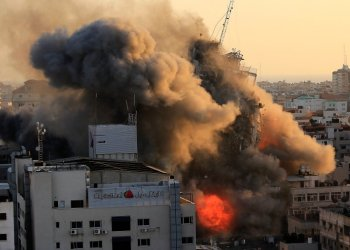 Heavy smoke and fire surround Al-Sharouk tower as it collapses during an Israeli air strike, in Gaza City on May 12, 2021. - An Israeli air strike destroyed a multi-storey building in Gaza City today, AFP reporters said, as the Jewish state continued its heavy bombardment of the Palestinian enclave. (Photo by QUSAY DAWUD / AFP)