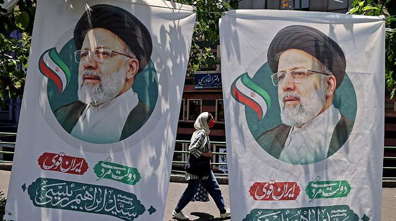 Una mujer iraní pasa junto a las pancartas del clérigo ultraconservador Ebrahim Raisi, en Teherán. | Atta Kenare / AFP