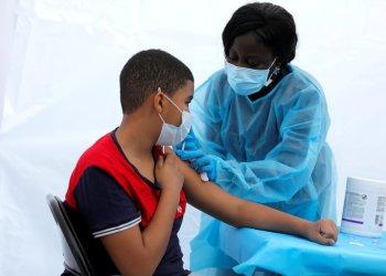 Justing Concepcion, de 12 años, recibe una dosis de la vacuna de Pfizer-BioNTech de manos de la enfermera Angela Nyarko, durante un evento de vacunación para adolescentes y adultos en el barrio del Bronx de Nueva York, el 4 de junio de 2021 (REUTERS/Mike Segar/File Photo)