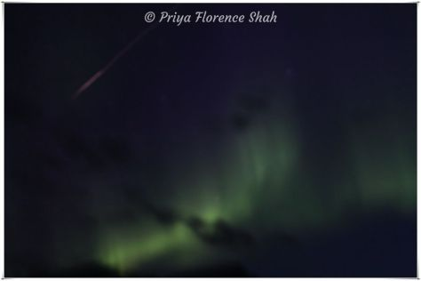 A meteor streaks across the sky as the Northern lights dance nearby