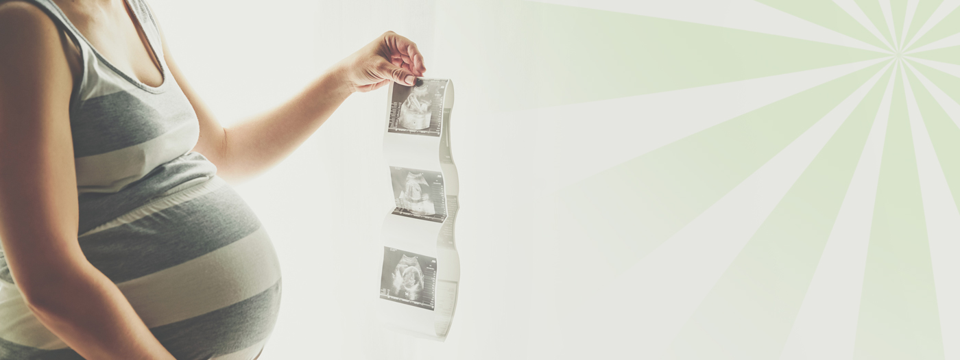 Pregnant woman holding ultrasound photos