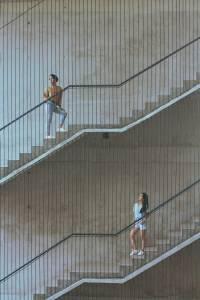 man in t shirt and blue denim jeans walking up the stairs