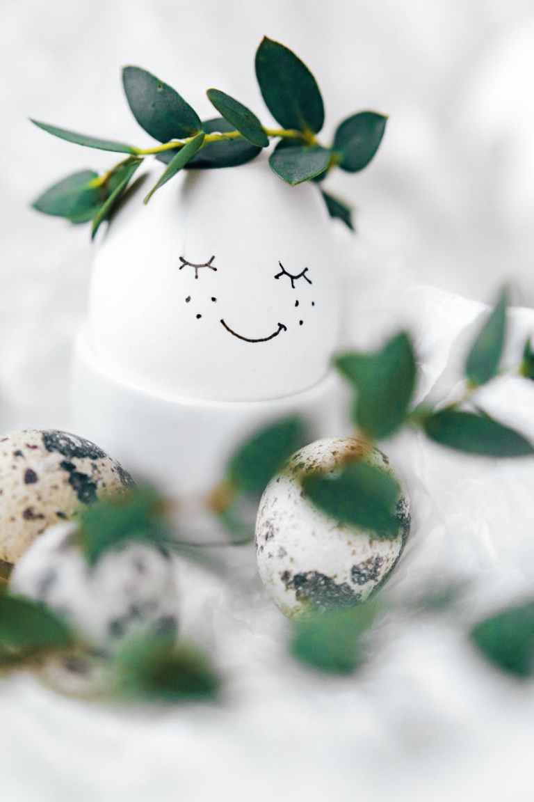 white egg with painted face and green leaves