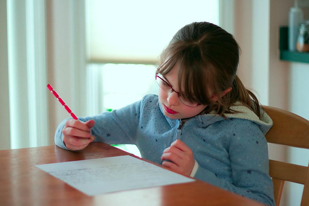 Photographie d'une enfant faisant ses devoirs avec l'aide à la scolarité de l'AHTOUPIE
