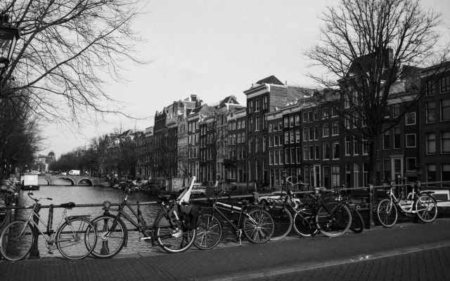 bikes parked on city embankment near canal and old buildings on cloudy day