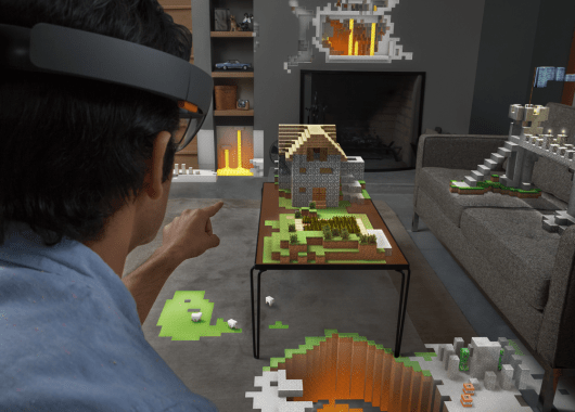 HoloLens - Augmented Reality. A man is wearing a hololens headset and using it to control a Minecraft world in his living room.