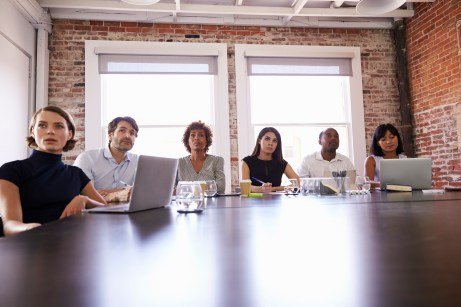 Businesspeople Listening To Presentation In Boardroom