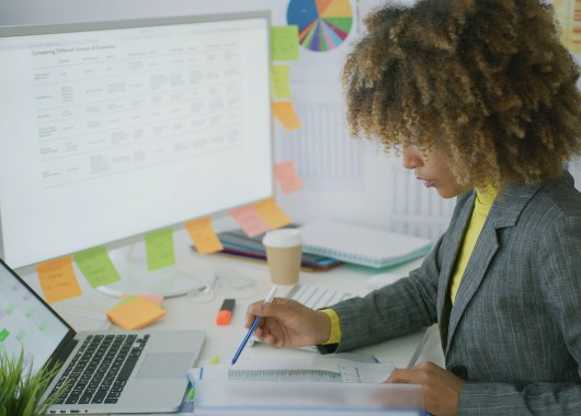 Confident stylish woman in formal clothing posing at working desktop with laptop and computer looking through paper documents.