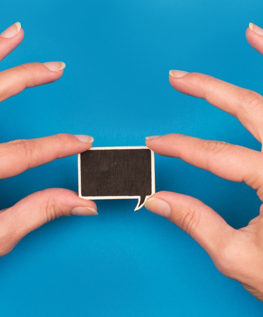 top view of two hands holding a wooden speech bubble on blue background, concept for communication