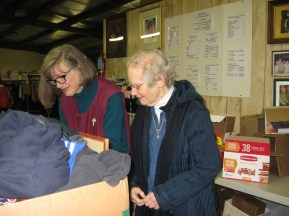 Sr. Carol helps counter volunteer, Jane Ankrom, check out a client's items.