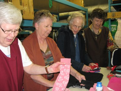 Sr. Carol helps to sort the children's clothing with, left to right, Barb Bax, Joan Brinkman, (Sr. Carol), and Faylene Knuffman