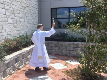 Deacon Terry blessing the memorial garden, building
