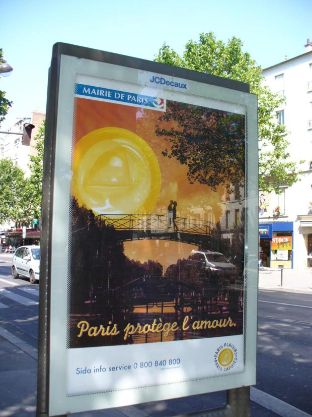 """A photo of a poster with romantic couple on a bridge in sunset light. """"Translation """"Paris Protects Love"""" -  AIDS/HIV awareness in Paris 2008."""