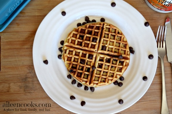 Overhead shot of a completed chocolate chip waffles recipe next to a fork and knife.