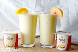 2 glasses of smoothie with slices of peaches on the glass and two containers of Yoplait Harvest Peach yogurt.