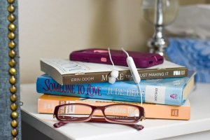 stack of three books, pair of glasses, cell phone, and bluetooth ear buds all sitting on a night stand.
