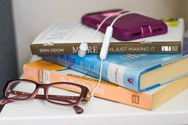 Stack of books, glasses, and phone on a nightstand.