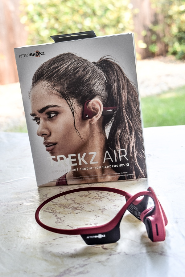 TREKZ Air Open Ear Buds in front of box, sitting on a table outside.