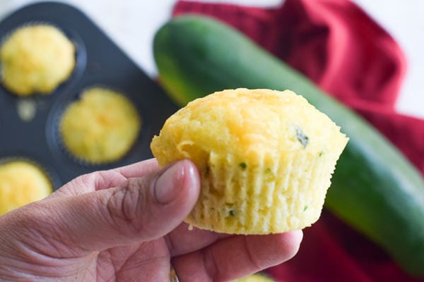 hand holding a cheesy cornbread zucchini muffin with batch of muffins and zucchini in background