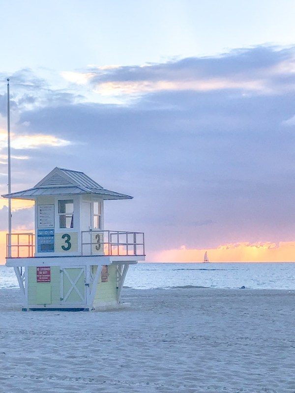 A yellow lifeguard tower on the sugar sand beach of Clearwater during sunset.