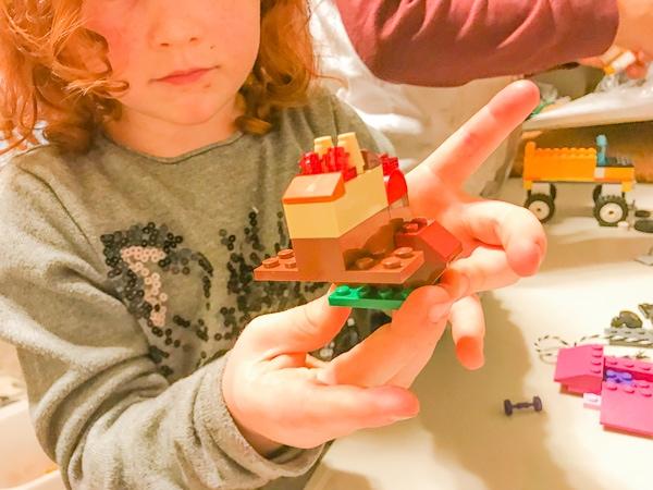 A little red headed girl holding a handmade Christmas ornament made of LEGO bricks.