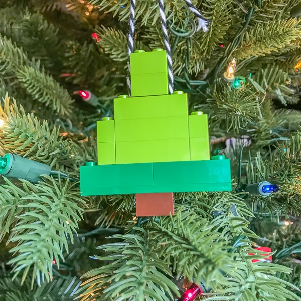 A christmas ornament made of green and grown LEGO bricks hanging on a tree.