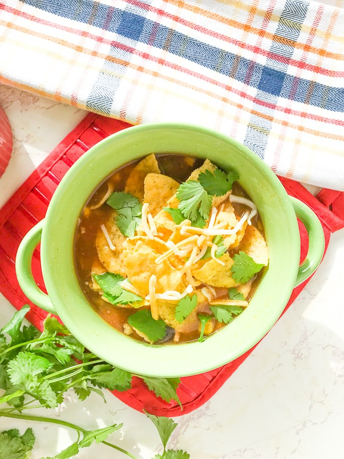 A bowl of instant pot chicken tortilla soup topped with chips, cheese, and cilantro.