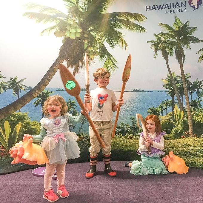 Three kids holding pops from the movie Moana.
