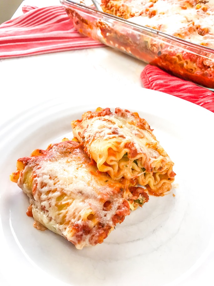 A close-up of two spinach lasagna rolls on a white plate.