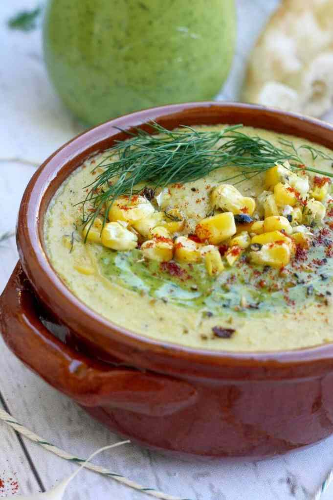 corn and zucchini soup in a red bowl.