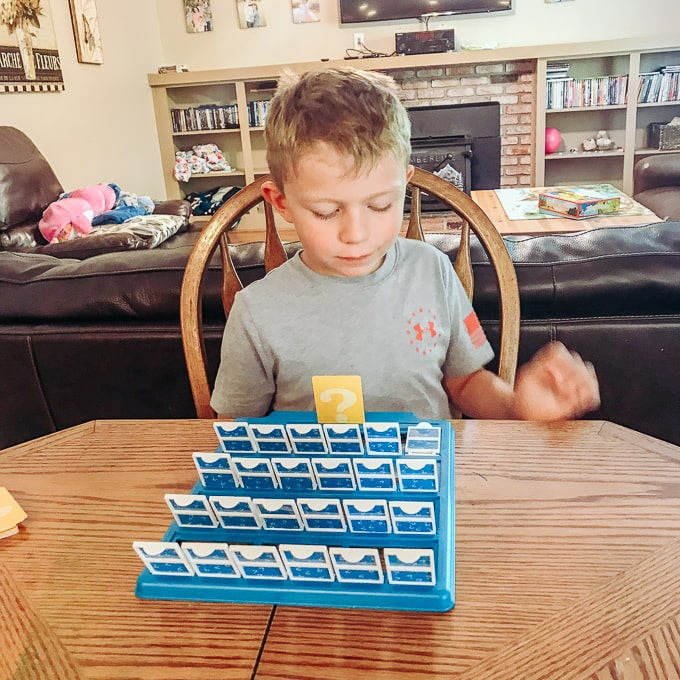 A boy playing guess who.