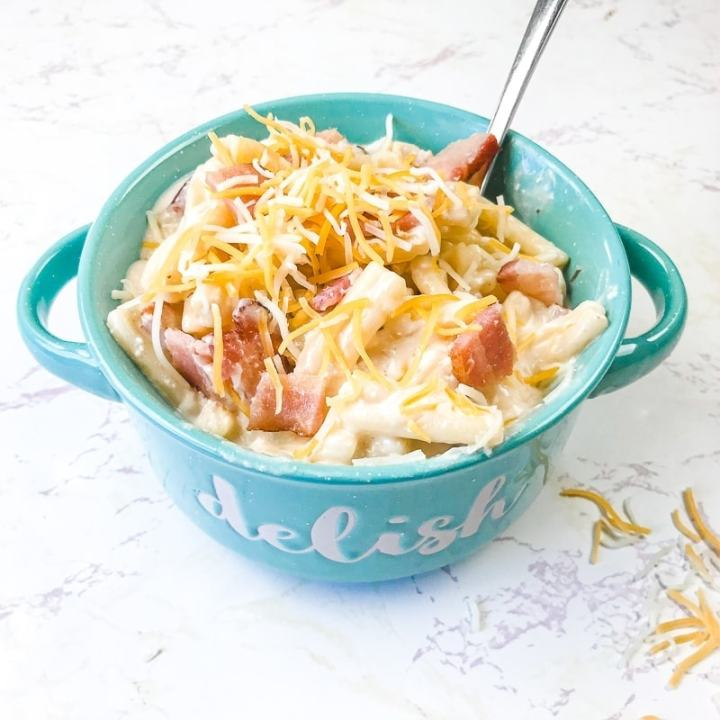 A teal bowl filled with instant pot crack chicken pasta topped with shredded cheese and bacon bits.