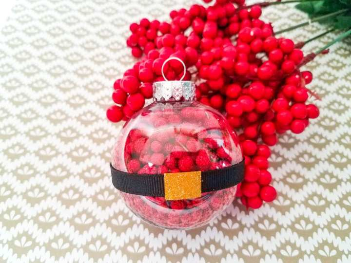 Santa belt ornaments lying in front of a pile of red balls used to fill the ornament.