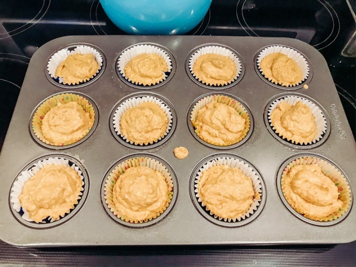 Pumpkin cornbread batter poured into a muffin tin filled with liners.