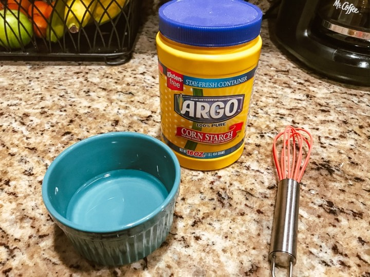 Small blue bowl, small whisk, and container of cornstarch.