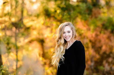 Young blond in black shirt with fall colors in background