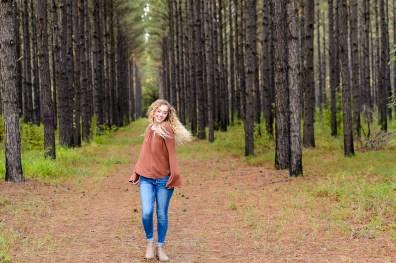 girl in jeans dances in the woods portrait