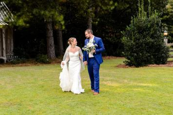 Bride and groom walk on lawn