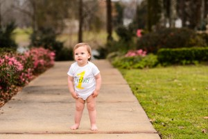 little blonde girl standing on walkway for one year photography session